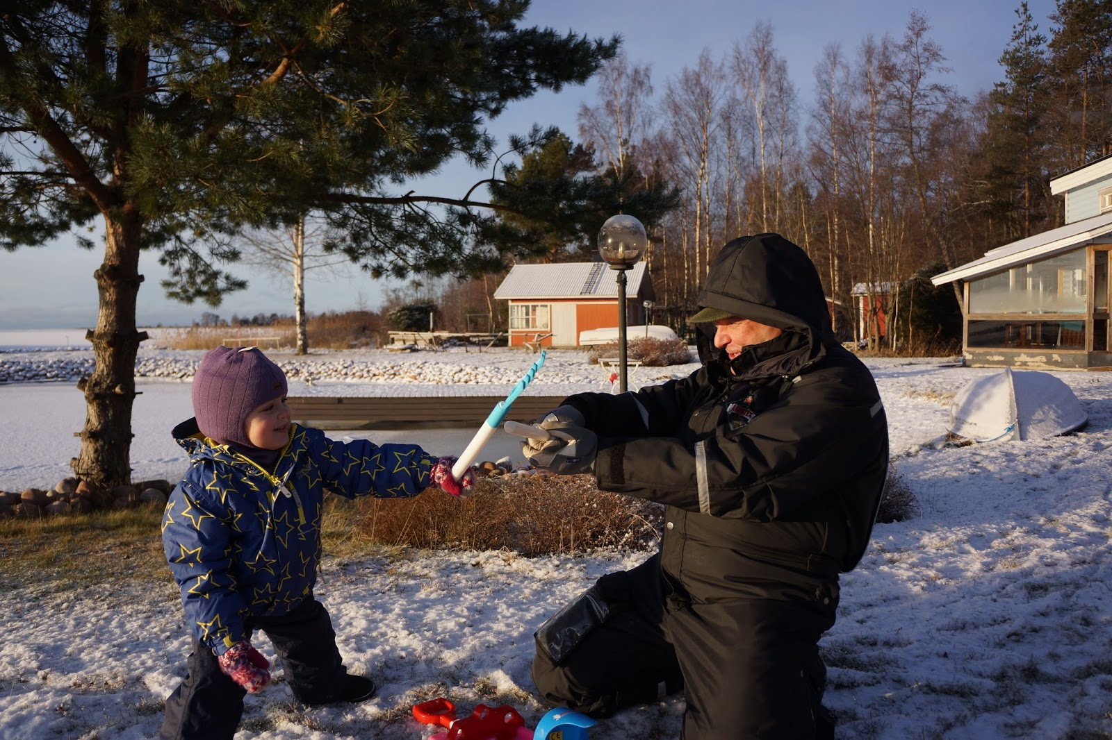 child playing with grand father in snow
