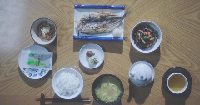 un desayuno tradicional japones, la caballa en un plato cuadrado, rodeada de platos redondos, sopa, té, arroz,  ensalada, un plato de habas, condimentos, encuertidos...