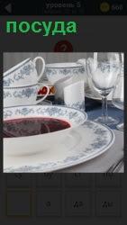 на столе стоит разная посуда, в тарелке налит суп из которого идет пар