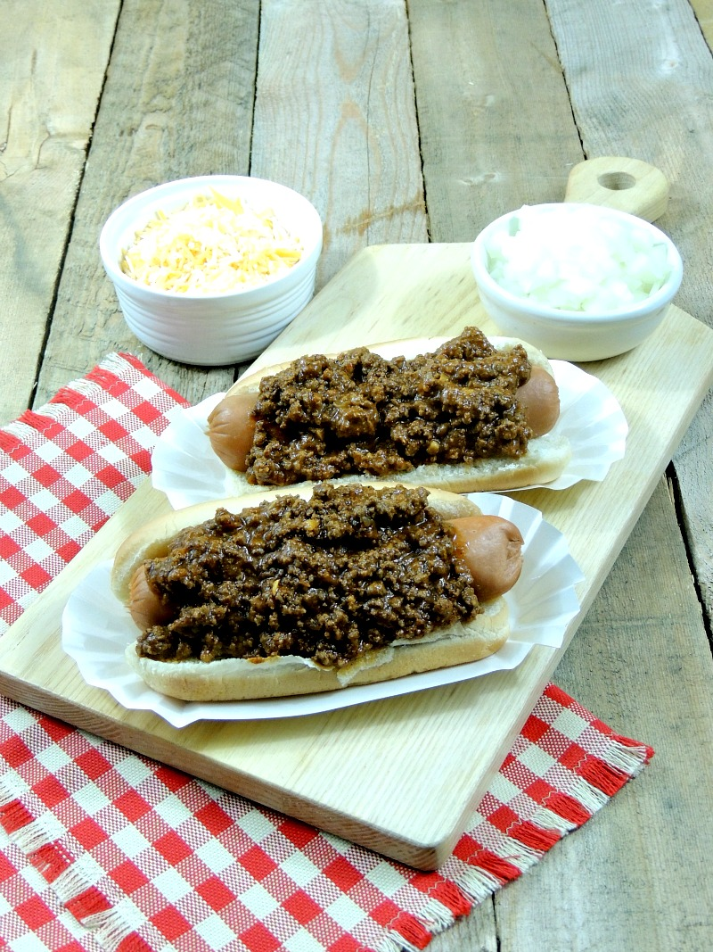 2 hot dogs with Coney Island Hot Dog Chili on a cutting board with bowls of chopped onions and shredded cheese on a wooden background with a red and white checkered napkin.