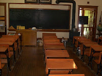 Old-fashioned classroom with wooden table and chairs and blackboard