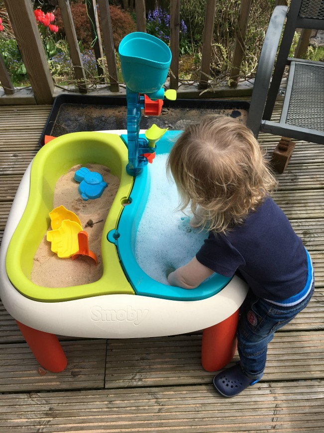 toddler with arms in bowl full of soapy water