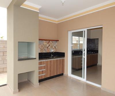 A churrasqueira da varanda gourmet é integrada com a cozinha da casa, recebendo o mesmo acabamento em marmoraria e marcenaria.