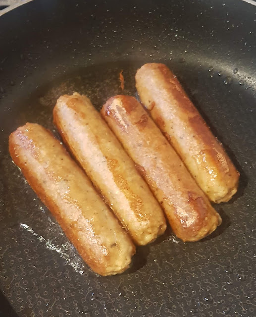 Four sausoyges cooking in a frying pan.