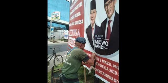 Seorang Kakek Jahit Kembali Baliho Prabowo-Sandi yang Robek