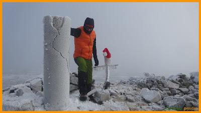 Cima del Pico Teleno junto al vértice envueltos en la niebla y el frío.