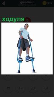 Мужчина идет на высоких ходулях в кроссовках и шортах, сохраняя равновесие