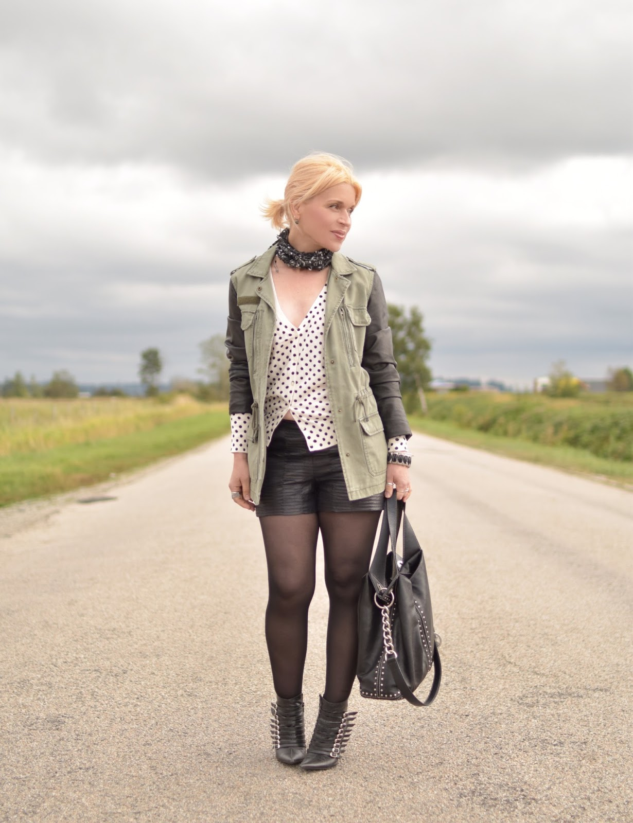 Monika Faulkner styles a polka-dot cardigan with an army jacket, faux-leather shorts, and buckle-embellished booties
