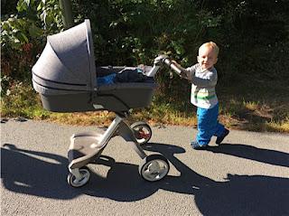 Das Christkind schiebt den Brudi im Kinderwagen