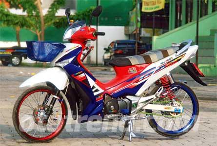 Foto Modifikasi Honda Supra Rombakan dengan kelir bendera belanda tersebut, yang disembur merata dan di tutup dengan stiker Wave i 125 atau motor supra X 125 versi Thailand. Pelek dibikin dua warna dengan Osaki merah dibagian depan dan Takasago biru dibagian belakang.