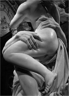 Descrição:Foto em preto e branco de parte de uma escultura em mármore: O rapto de Proserpina. O deus Hades sustenta a deusa Proserpina na altura dos ombros, nua, com o corpo em perfil ; a perna esquerda pousa levemente sobre a outra e produz sombra no joelho direito; o delicado pé esquerdo, voltado para baixo está no ar. A mão direita de Hades segura fortemente a coxa de Proserpina, os dedos pressionam a carne de aspecto firme; a outra mão de Hades enlaça vigorosamente a cintura da deusa, o dedo indicador afunda na carne lateral das costas e forma um L com o dedo polegar. No topo, parte das pontas dos cabelos cacheados de Proserpina ao vento, nas costas, uma sombra contrasta o brilho de um foco de luz sobre o ombro e, parte do braço em ângulo, revela uma porção do pequeno seio esquerdo próximo aos cabelos ondulados de Hades; a mão da deusa se lança a frente do corpo e atinge a cabeça de Hades. Entre os corpos vigorosos, um manto ondula em pregas. No teto, uma pintura com duas figuras humanas.