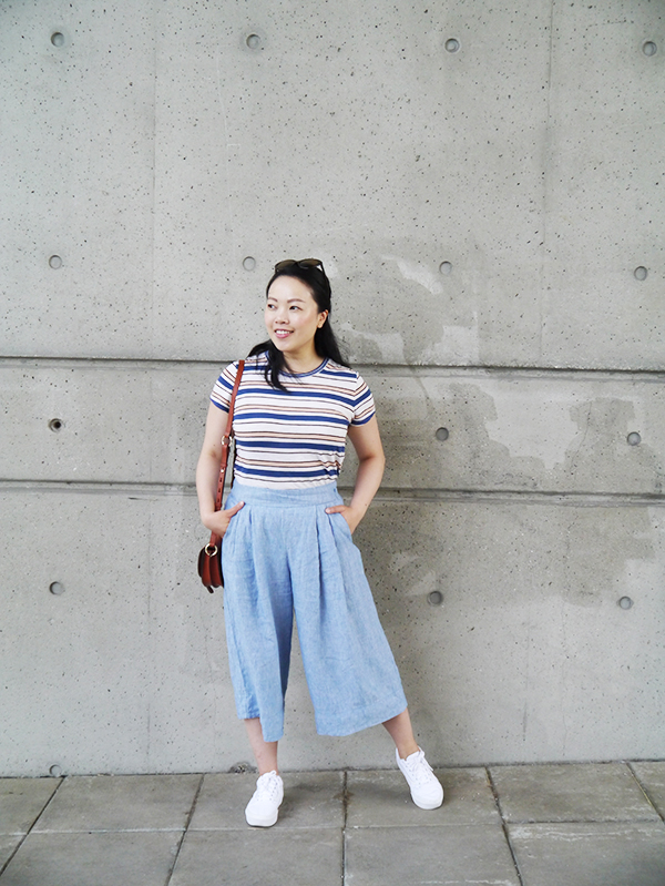 Vancouver beauty, life and style blogger Solo Lisa wears wide leg light blue linen pants from the Gap with a Madewell striped tee, cognac leather handbag from Tila March, and platform white Vans sneakers.