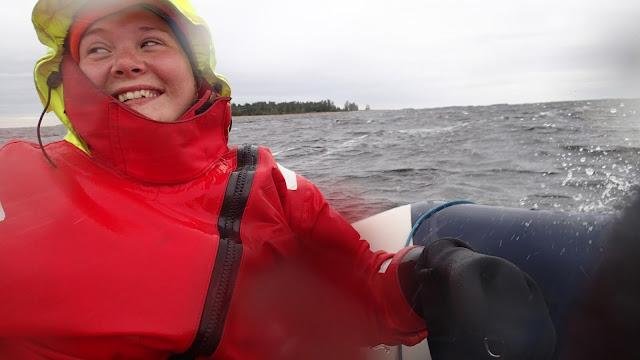Pelastautumispukuinen henkilö hymyilee kumiveneessä aallokossa