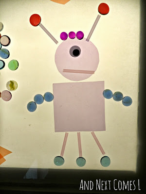 A robot made from loose parts on the light table from And Next Comes L