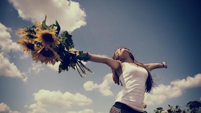 Chica con los brazos abiertos con flores en la mano