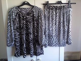 Foto minha com uma saia e blusa de padrões em tons de preto, cinza e branco.