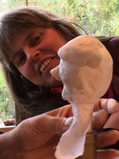 puppet maker looking at a puppet face in the making - at Corina Duyn's studio