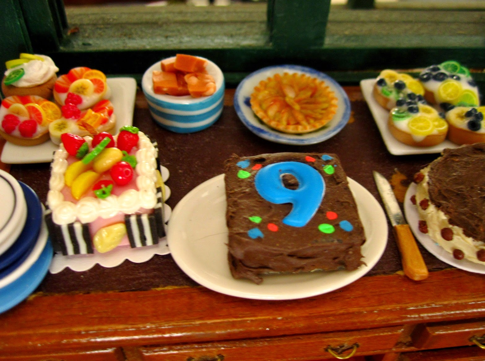 Selection of miniature dolls' house cakes arranged on a desk, including one with the number 9 iced on the top of it.