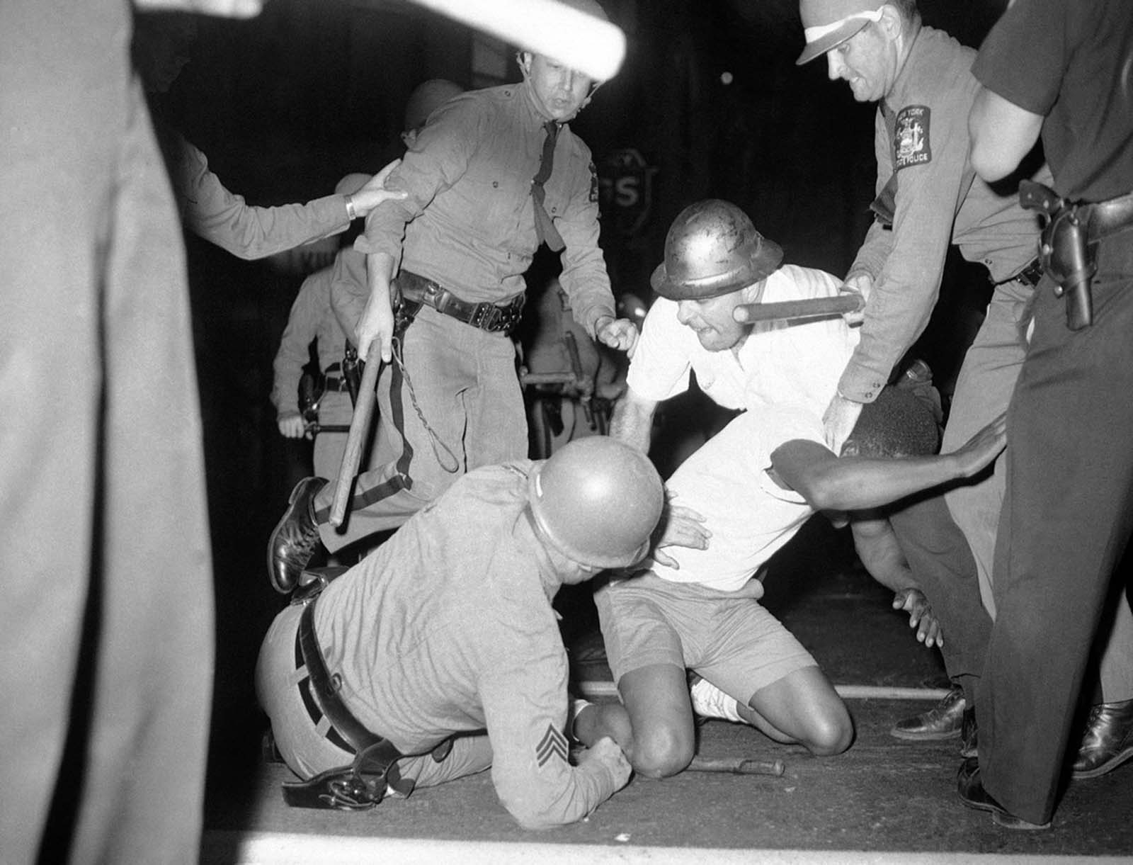 A police officer falls to pavement as he struggles to apprehend a man in Rochester, New York, July 25, 1964.