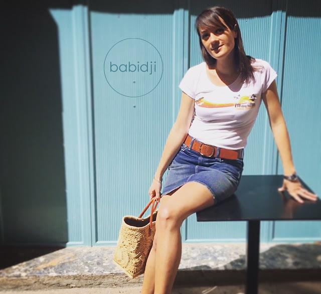 femme assise sur une table portant un t-shirt de la marque Carve Mauritius et un panier