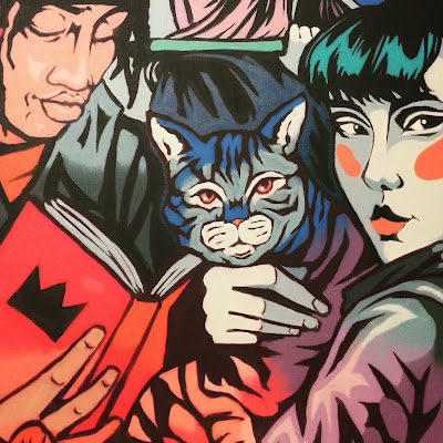 Mural featuring a cat, a Japanese girl and a man reading a book.