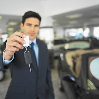 Car salesman holding car keys