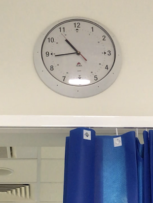 The view out of an A&E booth with a clock and blue clinical curtain visible
