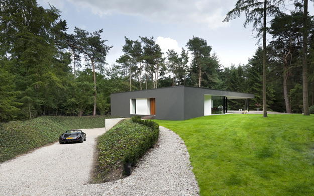 Photo of modern minimalist home as seen from the driveway with small black car parked