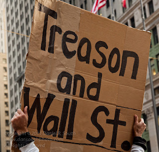 a photo of an occupy wall street sign that reads treason and wall street