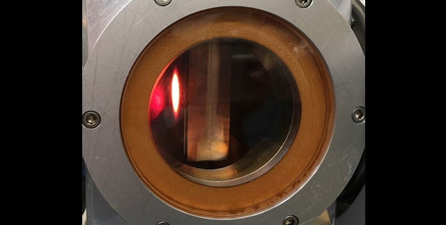 More than 2 kilowatts of proton beam impinging on the water-cooled, tungsten-reinforced beam stop at the end of the ECRIS acceleration column, as seen through its viewing portal.  CREDIT: Arthur E. Champagne