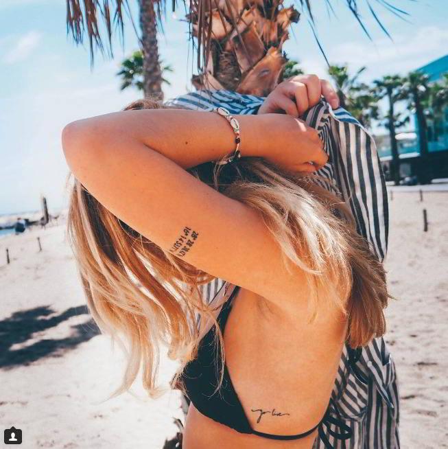 Foto de una chica en la playa con un tatuaje precioso en el brazo