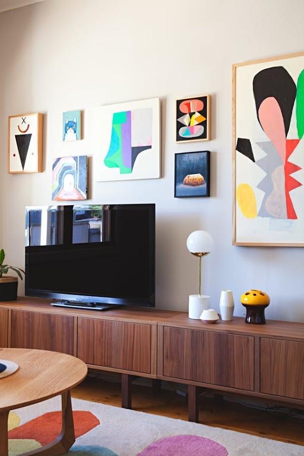 salón con tv plana y obras de arte en al pared