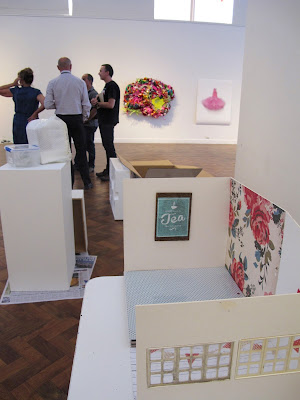 Dolls' house miniature scene on a table in a gallery during install, with gallery staff talking in the background.