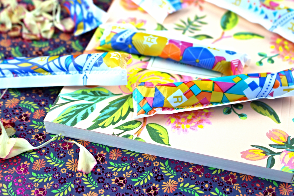 This photo shows several Tampax Pocket Pearls resting on an adorable floral designed Rifle Paper Company notebook.