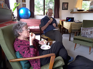 Mum and Dad eating pork buns in our lounge.  Mum is bringing hers to her mouth, Dad is smiling.