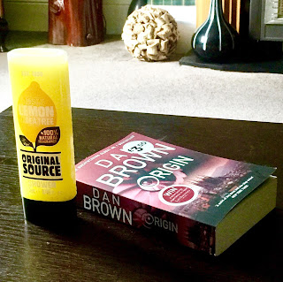 A rectangular clear plastic bottle filled with yellow liquid with a picture of a Lemon with Original Source in big bold black font with Lemon & Tea Tree in white font next to a rectangular book saying dan brown in white font on a brown rectangular table  on a bright background