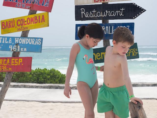 Niños en bañador frente a unos carteles de colares con distancias a ciudades del mundo