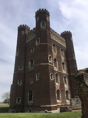 photo of red brick castle tower with turrets on each corner