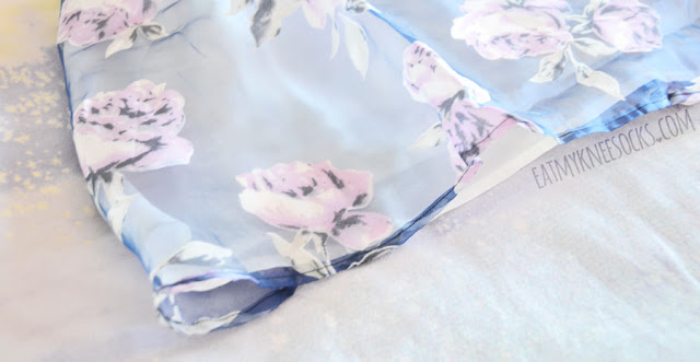 Details on the Dreamin' of Sunshine dress from Tobi, featuring a pastel blue sheer organza overlay with purple floral print on a flared bustier-style skater dress.