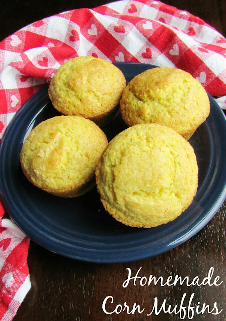 4 corn muffins on plate with gingham towel