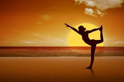 Moca-praticando-Yoga-na-praia-ao-por-do-sol