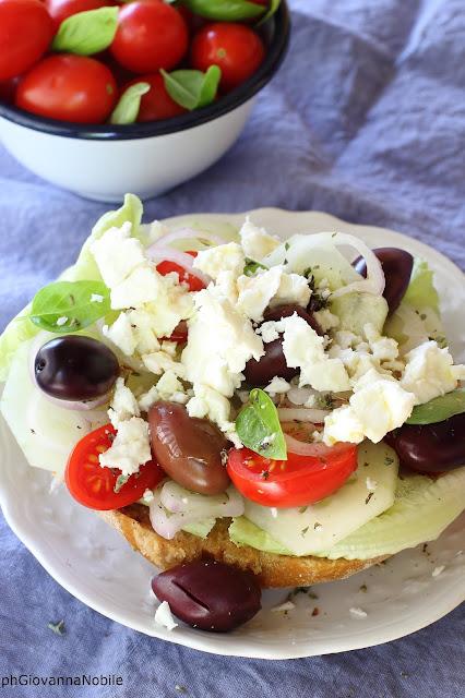 Insalata greca con lattuga, pomodori, cipollotti, cetriolo, feta, olive e.....friselle