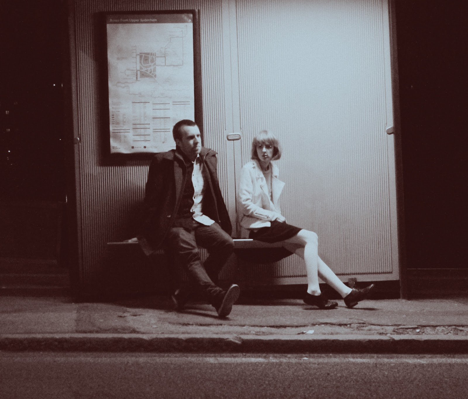 Rescue A Family - A man and woman sit at a bus stop.