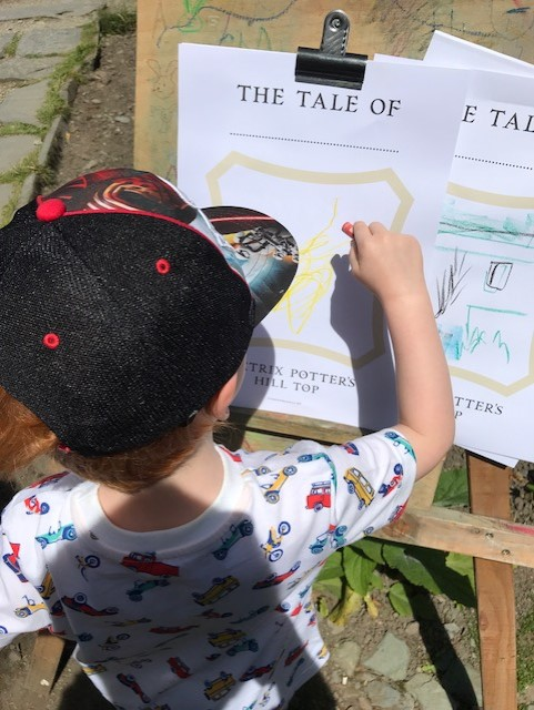 A little boy outside standing at an easel and drawing on a sheet titled 'the tale of'