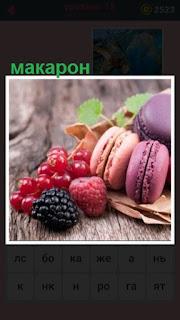 на столе лежат цветной макарон и несколько ягод