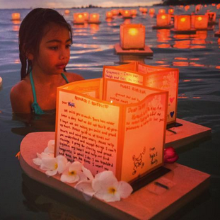 girl watches floating lanterns during a Lantern Floating ceremony honoring Memorial Day in Honolulu, Hawaii