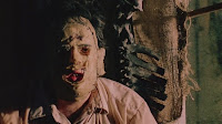 Leatherface sitting pensively by the window in The Texas Chainsaw Massacre (1974)