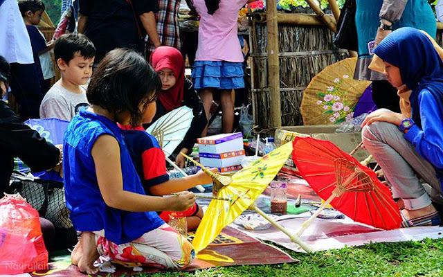 Anak-anak membuat motif pada tiap payung