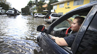Sandy Garcia sits in her vehicle on a flooded street in Fort Lauderdale, Florida, in 2015. (Credit: Joe Raedle / Getty Images) Click to Enlarge.