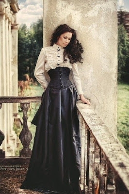 An example of an underbust corset used in steampunk victorian women's fashion. This woman wears her underbust corset with a ruffled high neck blouse and long black skirt.